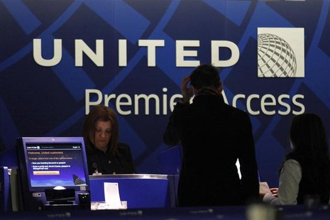 A worker from United attends to some customers during their check in process at Newark International airport in New Jersey , November 15, 20