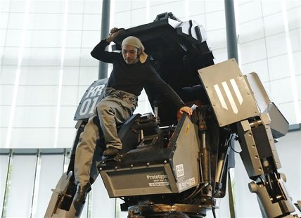 "Japanese artist Kogoro Kurata, inventor of the giant ""Kuratas"" robot, climbs out of its cockpit at an exhibition in Tokyo November 28, 2012."
