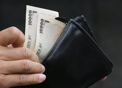 A man holds Japanese 10,000 Yen ($121) bank notes in front of a bank in Tokyo November 22, 2012. REUTERS/Kim Kyung-Hoon