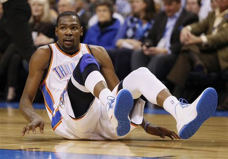 Oklahoma City Thunder forward Kevin Durant slides to the floor on a play against the Houston Rockets in the second half of NBA basketball ga