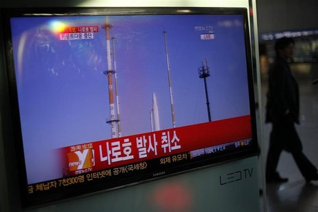 A passenger walks past a TV screen broadcasting the news that the launch of Korea Space Launch Vehicle-1 (KSLV-1), or Naro, was cancelled du