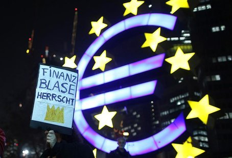 A woman holds a sign in front of the Euro currency sign next to the European Central Bank (ECB) headquarters during a demonstration against