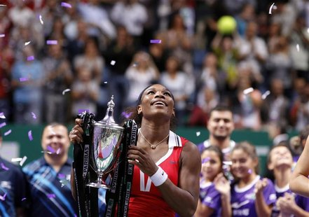 Serena Williams of the U.S. celebrates with the trophy after her victory against Russia's Maria Sharapova after their final WTA tennis champ