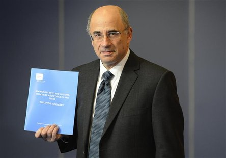 Lord Justice Brian Leveson poses with an executive summary of his report following an inquiry into media practices in central London Novembe