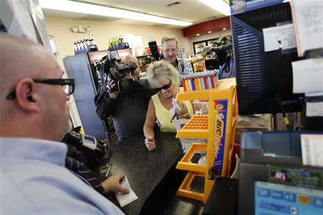 Manager Bob Chebat (L) talks with Barbara Altergott after checking her Powerball lottery ticket at the 4 Sons Food Store and Chevron gas sta