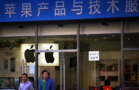 Customers walk out of a store selling and advertising Apple products, including both the iPhone 4 and iPhone 5, in central Beijing September