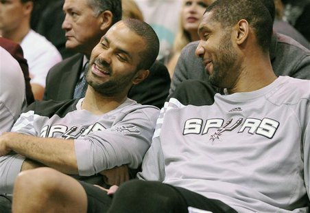 San Antonio Spurs point guard Tony Parker (L) and center Tim Duncan talk on the bench during the second half of their NBA basketball game ag