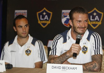 Los Angeles Galaxy's David Beckham (R) answers media queries while his teammate Landon Donovan watches during a news conference in Manila De
