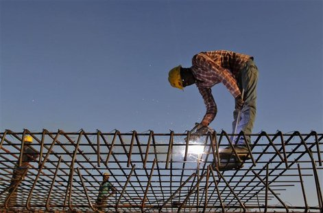 A worker welds iron rods at the construction site of a commercial complex in the western Indian city of Ahmedabad November 29, 2012. India's