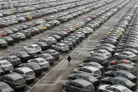 An employee walks past new cars at the parking lot of Changan Ford Mazda Automobile Co. Ltd, Ford Motor's joint venture in China, in Chongqi