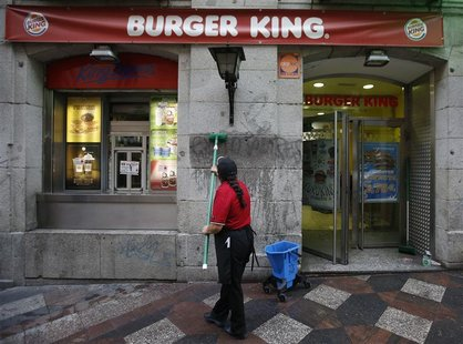 "A woman cleans graffiti reading ""Exploiters"" from the wall of a Burger King restaurant in downtown Madrid November 15, 2012. REUTERS/Andrea"