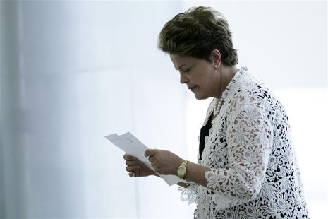 Brazil's President Dilma Rousseff reads a piece of paper at an event for the announcement of measures to expand the Affectionate Brazil Prog