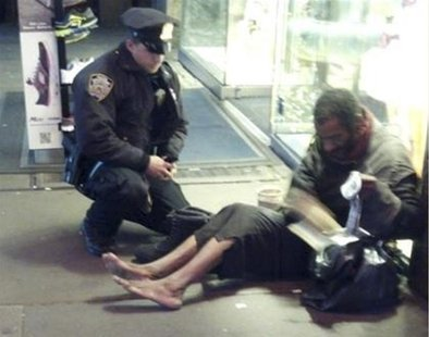 New York police officer Larry DePrimo gives a homeless man a pair of boots and socks in Times Square in this November 14, 2012 handout photo