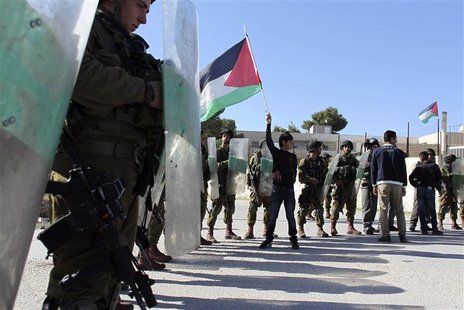 A Palestinian youth (C) waves a flag in front of Israeli soldiers during a demonstration in the West Bank village of al-Masara near Bethlehe