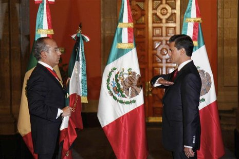 Mexico's outgoing President Felipe Calderon (L) holds the national flag as Mexico's new President Enrique Pena Nieto salutes during a midnig