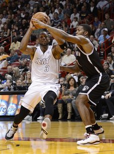 Miami Heat's Dwyane Wade (L) is defended by Brooklyn Nets's Joe Johnson during the first half of their NBA basketball game in Miami, Florida