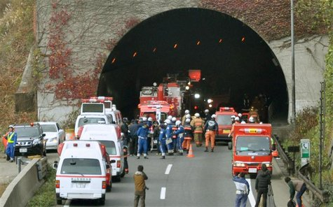 Police officers and firefighters gather in front of the Sasago Tunnel on the Chuo Expressway in Otsuki, Yamanashi prefecture, in this photo