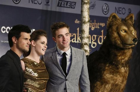Cast members Robert Pattinson (R), Kristen Stewart (C) and Taylor Lautner pose for pictures before the German premiere of The Twilight Saga: