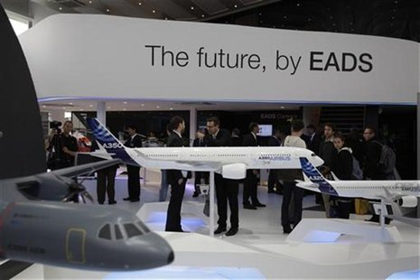 Visitors look at aircraft models at the EADS booth during the ILA Berlin Air Show in Selchow near Schoenefeld south of Berlin, September 13,