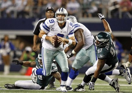 Dallas Cowboys quarterback Tony Romo scrambles as Philadelphia Eagles defensive tackle Cullen Jenkins is unable to make the tackle in the fi
