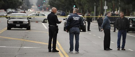Los Angeles police and robbery homicide detectives investigate the shooting scene where four people were shot and killed in Northridge, Cali