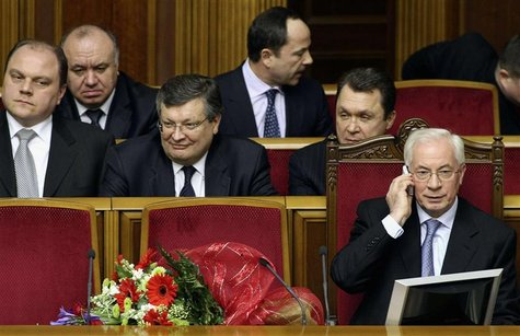 Then Ukrainian Prime Minister Mykola Azarov (R, front) talks on the phone after he was appointed as prime minister in Kiev in this March 11,