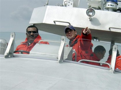 U.S. Coast Guard Coxswain Petty Officer 2nd Class Terrell Horne (R) points the way as Lt. Colonel. Rasheed Mansoor R. M. Al-Borashid, of Qat