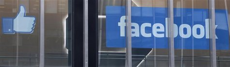 "The Facebook ""thumbs up"" icon and logo are displayed in a window at the offices of J.P. Morgan in New York City, New York, May 4, 2012. REUT"