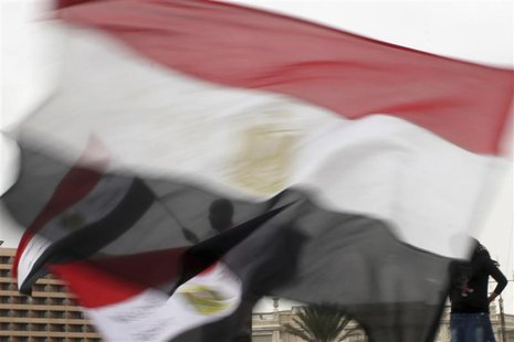 Anti-Mursi protesters, seen through Egyptian flags, chant anti-Mursi slogans in Tahrir square in Cairo December 4, 2012. REUTERS/Asmaa Wagui