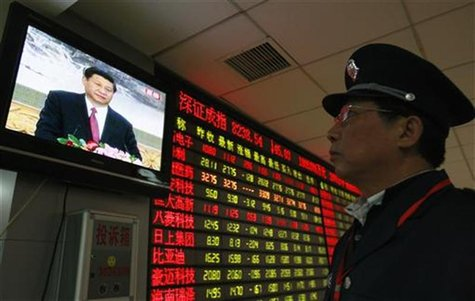 A security guard watches a screen showing newly-elected General Secretary of the Central Committee of the Communist Party of China (CPC) Xi