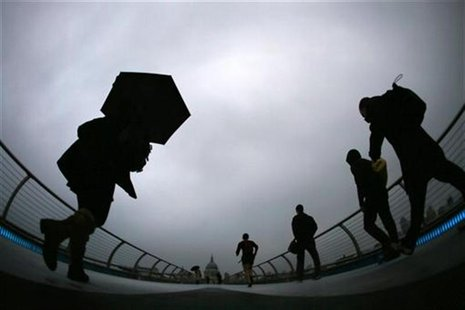 Commuters cross the Millennium Bridge during a rainy morning, towards the financial district the City of London November 27, 2012. REUTERS/S