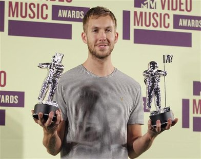 "DJ Calvin Harris poses backstage with statuettes after winning the award for ""Best Electronic Dance Music Video "" at the 2012 MTV Video Musi"
