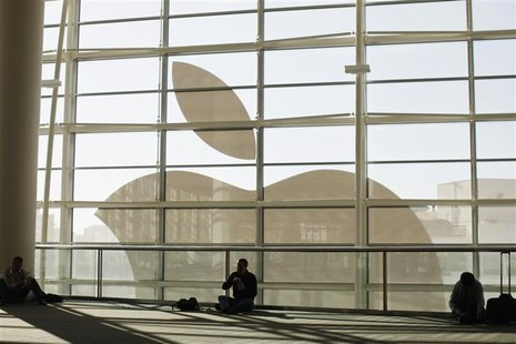 Attendees sit in front of an Apple logo during the Apple Worldwide Developers Conference 2012 in San Francisco, California June 11, 2012. RE