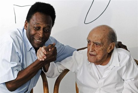 Brazilian soccer legend Pele (L) holds the hand of architect Oscar Niemeyer during a news conference in which they presented the plans for t