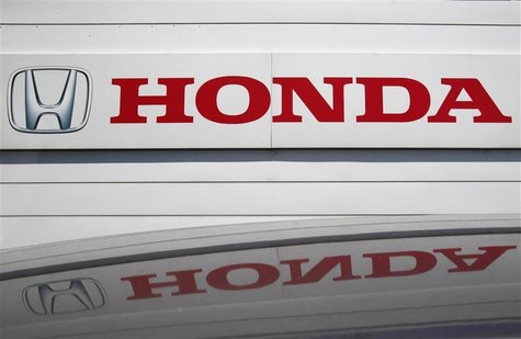 A logo of Honda Motor Co is reflected on a roof of a vehicle at a Honda dealer in Kawasaki, south of Tokyo July 31, 2012. REUTERS/Yuriko Nak