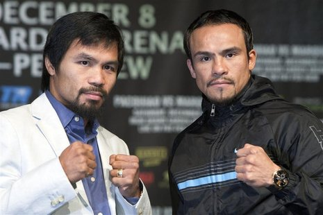 Filipino boxer Manny Pacquiao (L) and Juan Manuel Marquez of Mexico pose during a news conference at the MGM Grand in Las Vegas, Nevada Dece