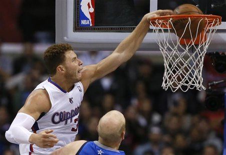 Los Angeles Clippers Blake Griffin (L) slam dunks over Dallas Mavericks Chris Kaman during their NBA basketball game in Los Angeles, Califor