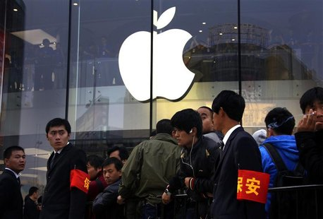 Security staff watch over a crowd gathered for the opening of a new Apple store in Beijing's Wangfujing shopping district October 20, 2012.