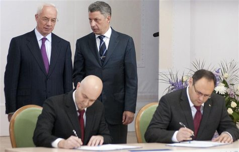 Ukrainian Prime Minister Mykola Azarov (L) and Energy Minister Yuri Boiko (2nd R) talk as Vladislav Kaskiv (R), the head of Ukraine's state