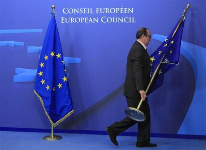 An employee at the EU council adjusts European Union flags at the entrance of the council headquarters for an European Union leaders summit