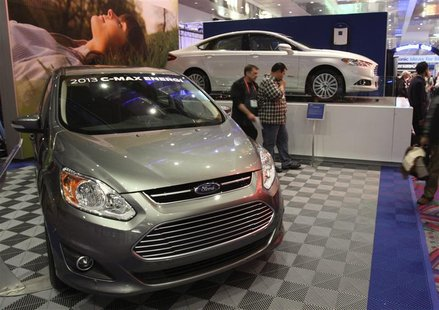 The 2013 Ford C-Max Energi (L) and 2013 Ford Fusion Energi hybrids are displayed in the lobby of the Las Vegas Convention Center during the