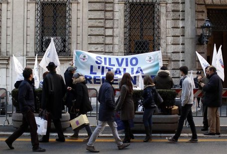 "Residents walk past a banner reading ""Silvio, Italy believes in you"" hung outside former Prime Minister Silvio Berlusconi's home in central"