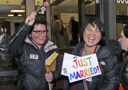 Junia Ribeiro (L), 51, and Patty Oh, 43, celebrate as they leave the King County Administration Building shortly after getting their marriag