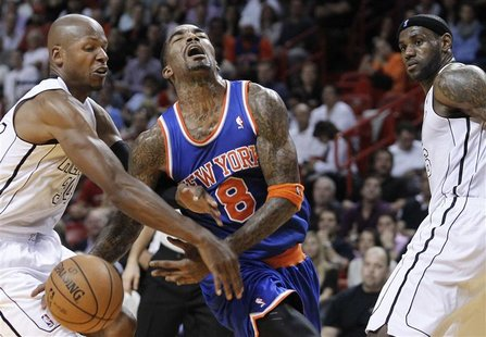 Miami Heat's Ray Allen (L) fouls New York Knicks' J.R. Smith (C) as the Heat's LeBron James (R) looks on in the send half of their NBA baske