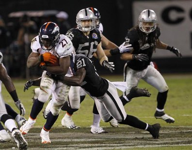 Denver Broncos running back Knowshon Moreno is tackled by Oakland Raiders cornerback Ron Bartell during their NFL football game in Oakland,