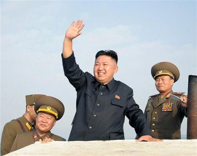 North Korean leader Kim Jong-Un (C) waves as he visits military units on islands in the most southwest of Pyongyang in this picture released