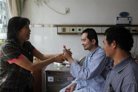 Zhang Tingzhen (C) is given a doll to play with by his mother Wei Xiuying while sitting beside his father Zhang Guangde at a Shenzhen hospit