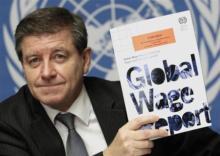 Guy Ryder, Director-General of the International Labor Organization (ILO) poses with a copy of the Global Wage Report after a news conferenc