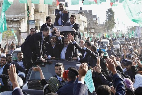 Hamas chief Khaled Meshaal (front L) waves to the crowd as he rides in a car beside senior Hamas leader Ismail Haniyeh (front R) in Gaza Dec