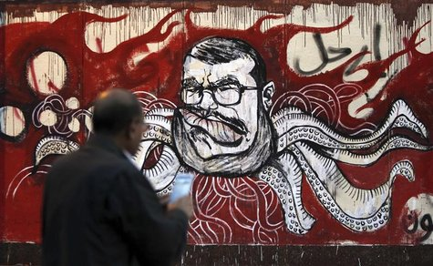 "A man take a picture of a mural of Egypt's President Mohamed Mursi and with Arabic words that reads ""Leave"" on the wall of the presidential"